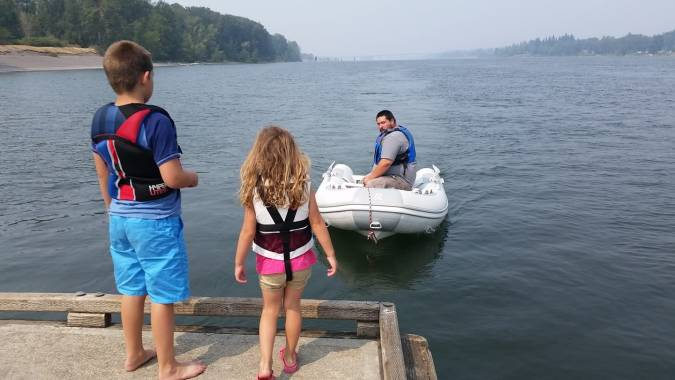 A boy and a girl standing on a dock watching their father approach in an inflatable dinghy, and island with trees in the background