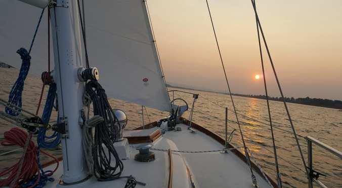 A view forward off the bow of the sailboat Mosaic sailing on the Columbia River with a gorgeous sunset on the horizon