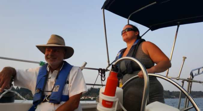 A woman at the helm of a sailboat named Mosaic, looking forward on the boat, with an instructor sitting in front of her smiling at the camera