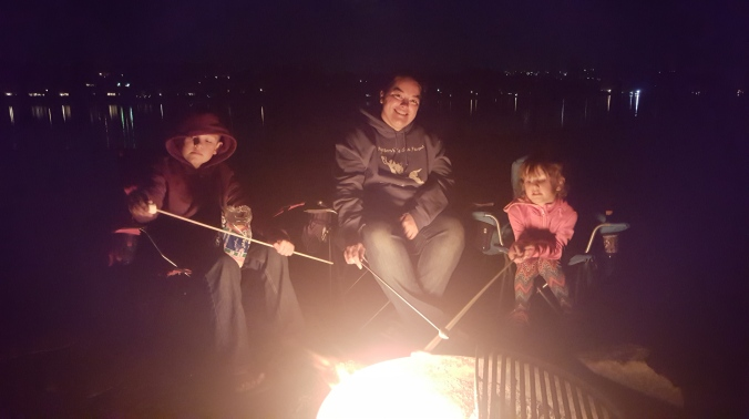 Mom, son, and daughter sitting around a campfire at night