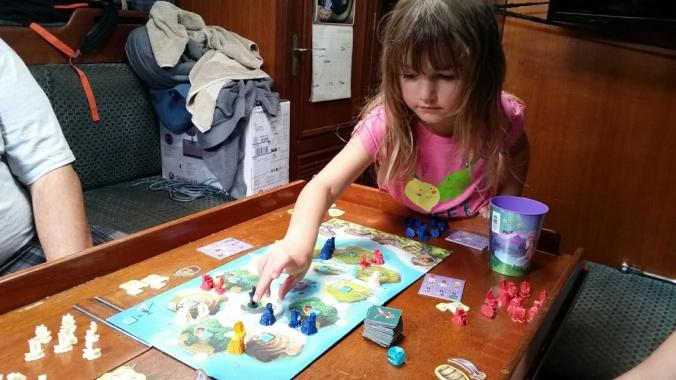 young girl playing Settlers of Catan Junior on a sailboat