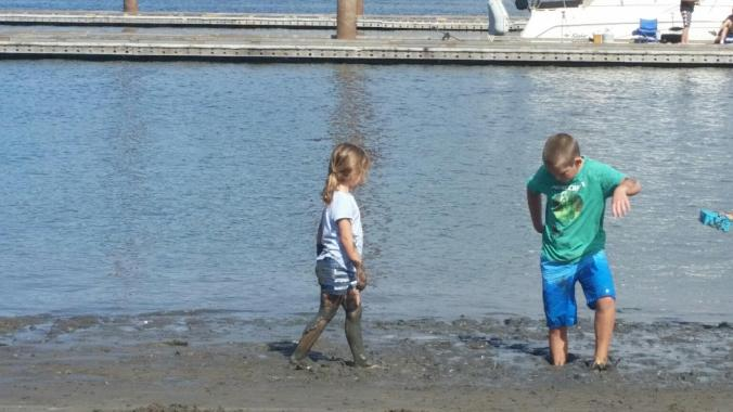 a boy and a girl playing in the mud along the riverbank