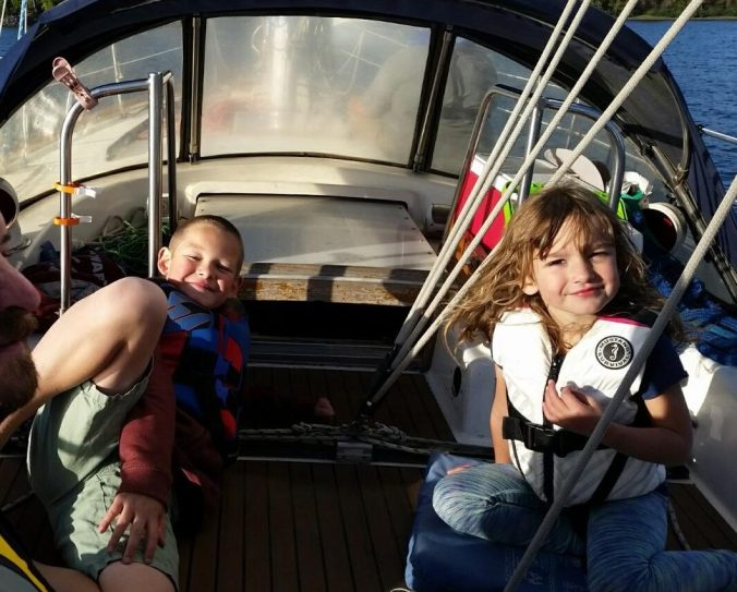 A boy and a girl in the cockpit of a sailboat under sail.