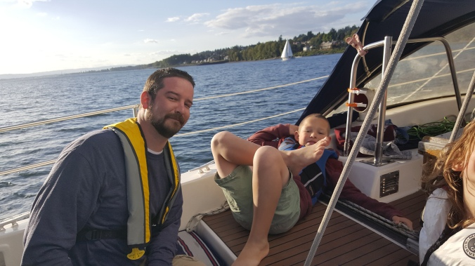 A man and a boy relaxing in the cockpit of a sailboat while sailing