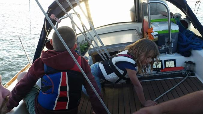 Two kids in the cockpit of a sailboat while sailing.
