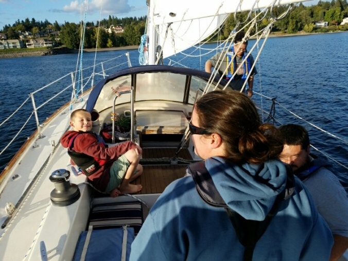 A woman at the helm of a sailboat under sail, with kids enjoying the ride