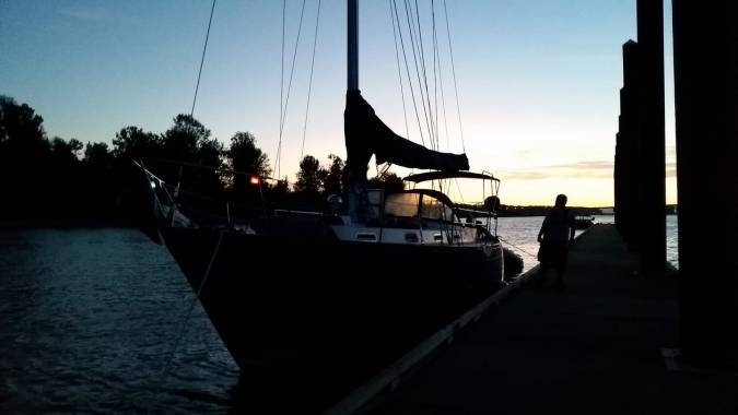 Sailboat tied to a dock at dusk