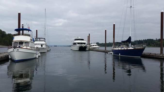 Several boats, including the blue sailboat Mosaic, tied to the dock at Government Island on the Columbia River
