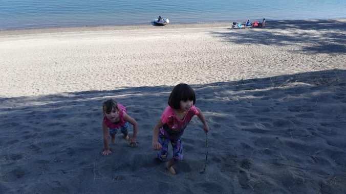 Two girls playing in the sand on a large sand dune on the Columbia River