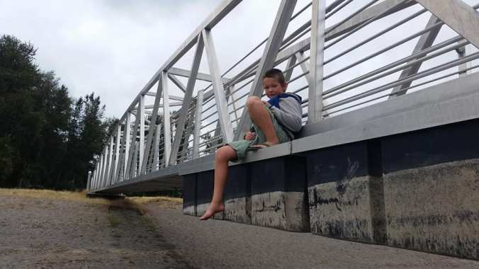 Boy hanging out, sitting on the outside of a dock ramp wearing a lifejacket and shorts