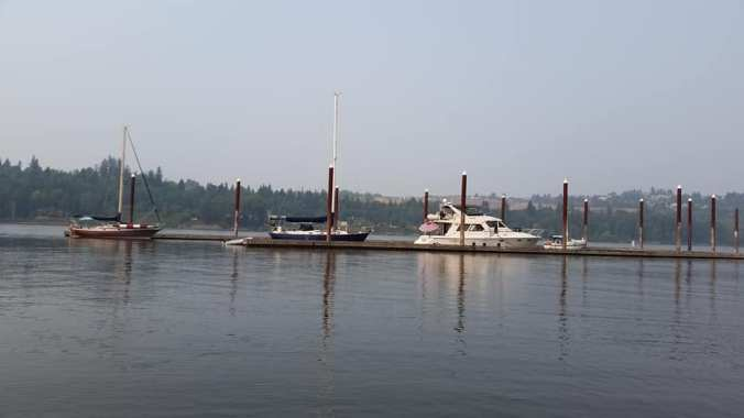 Two sailboats and a large power boat tied up at dock on the Columbia River
