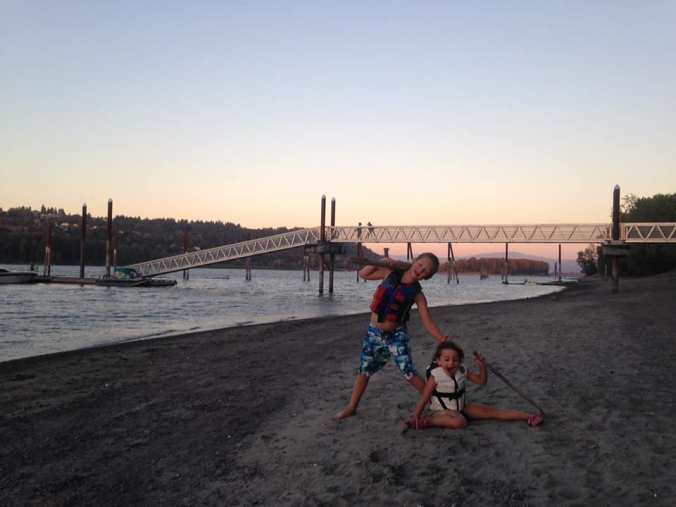 Boat Kids- two kids playing on a beach with a pretty dock in the background and a beautiful sunset