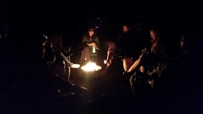 Large group of adults sitting around a campfire in the dark