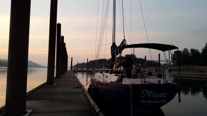 Sailboat tied to a dock with a beautiful sunrise in front of it