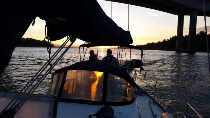 Sailboat with sail down motoring under a bridge as the sun sets behind the boat