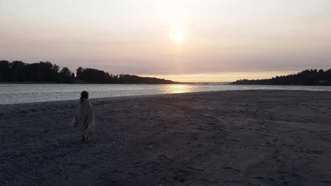 Young girl stands on a beach wrapped in a towel in a regal pose watching the sunset