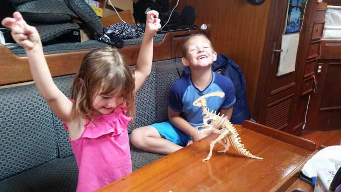 Kids cheering with a model dinosaur on the table, just built.