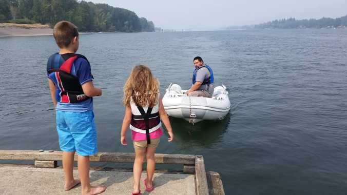 A boy and a girl standing on a dock watching their father approach in the inflatable dinghy