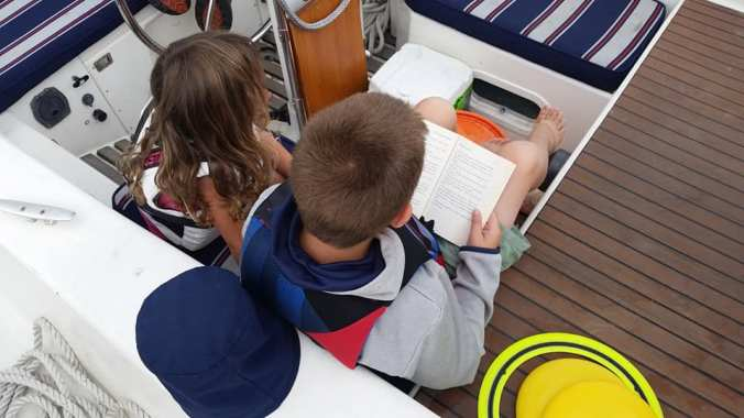 Boy sits in the cockpit of a sailboat next to a younger girl reading a book to her.