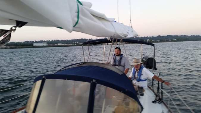 Looking back over the dodger of a sailboat at two men in the cockpit