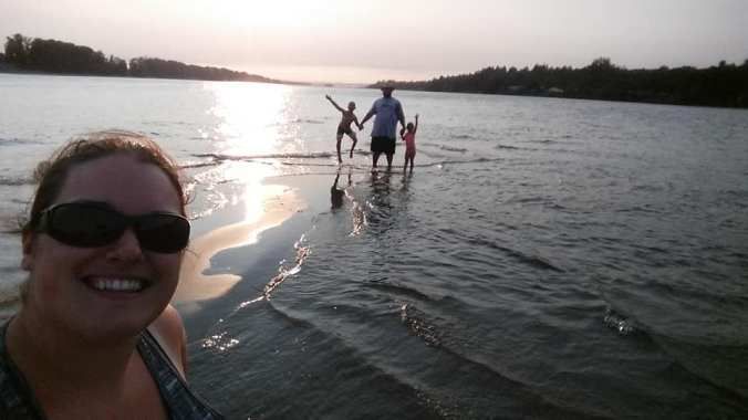 mom taking a selfie as dad and two kids stand silhouetted in the background standing in shallow water with the sun behind them