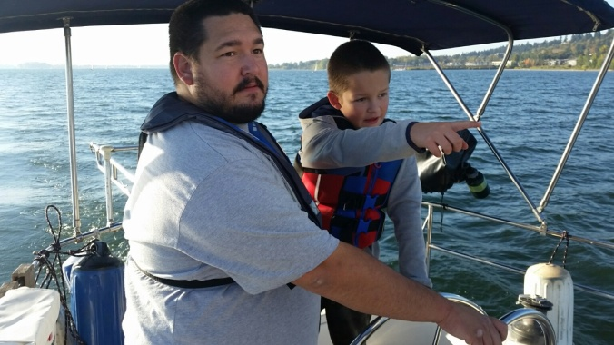 Boy steers the sailboat underway.