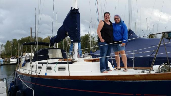 Two women standing on the bow of a Fuji 40 sailboat arm around each other for the photo