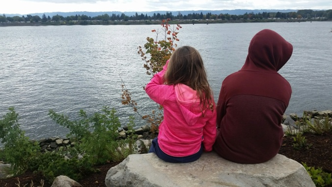 A boy and a girl sit side by side on a large rock overlooking the Columbia River.