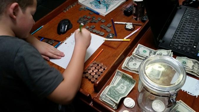Evan counts his cash aboard SV Mosaic - November 2018