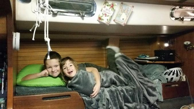 two boat kids in the pilot berth of a sailboat where they live