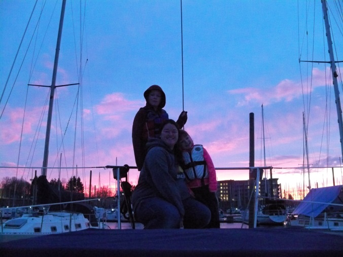 A woman and her two kids grab a photo on the bow of their sailboat, their home, with a beautiful March Sunset in Portland Oregon in the background