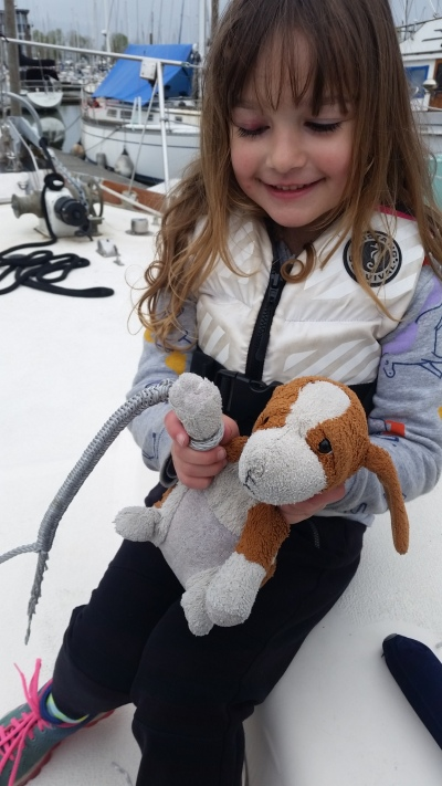 A girl and her stuffed dog help with splicing for the family's Dyneema lifeline project