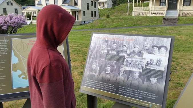Evan studies an informational sign at Fort Columbia