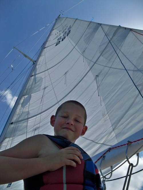 Our son Evan smiles at the camera with the large mainsail of our Fuji 40 sailboat rising into the sky behind him