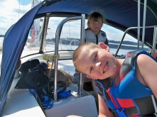 SV Mosaic kids smiling and having fun as we sail our boat through the Tacoma Narrows down to Anderson Island
